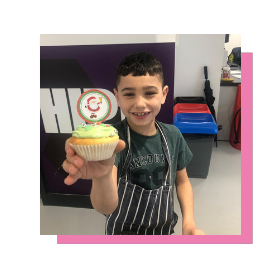 Lucas, a Junior member, holding his Christmas fairy cake with green icing, colourful ball decorations and a Santa topper